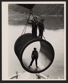 [Four men, three standing on top and one standing inside, riding on large casing section of pipe suspended by cable as it is moved into position by a crane, reservoir in the background during construction of the Grand Coulee Dam, Washington]