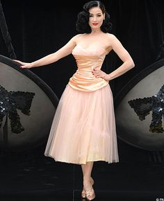 Dita von Teese with a ballet inspired dress. The skirt has an elegant length, which nicely balances the decollete. The shoes are also very lovely.