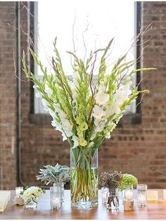 This vertical centerpiece was put together with stems of  gladiolus and tall branches (willow, maybe) in a narrow glass vase. Good idea for a card, escort card, or entrance table. Could also place on pedestal anywhere that needs more decoration. | Chicago Love Photographer_Caili Helsper