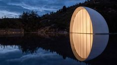 """An illuminated semicircular window above a pool of water simulates """"a moon that never sets"""" on the roof of a ceremonial hall designed by Syn Architects, in the dramatic landscape surrounding Mount Tai in China."""