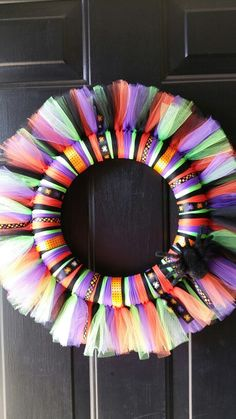 Halloween Tulle Wreath I made using orange, black, green and purple tulle. Added halloween ribbon and a fuzzy spider. Used 12 inch Styrofoam wreath.