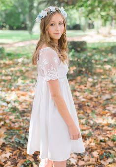 Cette charmante demoiselle d'honneur porte notre robe Lucie en ivoire avec la dentelle sur les épaules et une couronne de fleurs Elsa pour une note givrée à votre mariage.