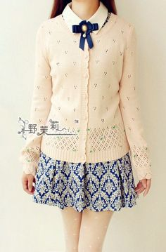 Cute outfit with the patterned dress, creme cardigan, and the white collar with a ribbon.