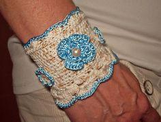 Confeccionado em crochê de linha mesclada e detalhes em azul, com aplicação de pérolas nas flores e para abotoar.
