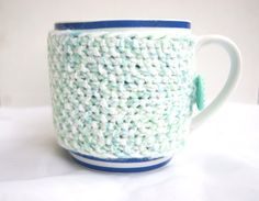 Hand knitted pastel green with white cup cozy with green flower button