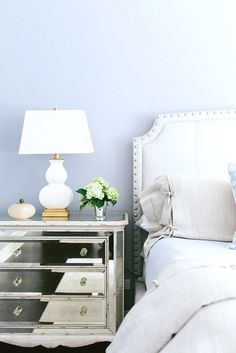 Bedside table with white lamp and small bouquet of flowers