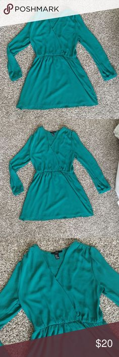 "Beautiful long sleeve green dress size M Gorgeous flowy long sleeve green dress. Size medium from ""XXI"" brand. Elastic waist and flowy skirt and sleeves. Sleeves have a button to keep them cinched. Dress has a lining. Also a button on the front that you can leave buttoned to be more conservative  or unbuttoned to show off cleavage. XXI Dresses Long Sleeve"