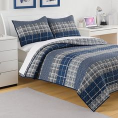 The Riviera quilt brings patchwork plaid patterns together in masculine tones of gray and navy blue for a classic yet updated look. Made from 100-percent cotton, it reverses to a textured gray and white plaid and is finished with a simple navy border.