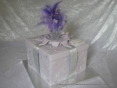 Lilac coloured birthday surprise present celebration cake. Decorated with silver sugar stars and edible name tag. Finished with silver glitter ribbon and topped with a purple and silver wired explosive topper with glittered number 60