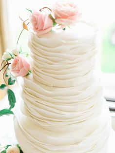 Elegant three tier white wedding cake decorated with fresh pink roses - Image by Belle and Beau Photography - An Ian Stuart 'Sapphire' bridal gown for a classically romantic wedding at Rudding Park in Harrogate with a Dahlia bouquet and pink bridesmaid dresses www.rockmywedding.co.uk