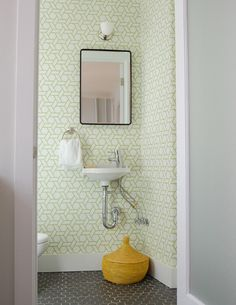 Fun white and green powder room with Manuel Canovas Trellis Wallpaper and wall mounted sink. Simple, black edged mirror, gray hexagonal floor tiles and yellow woven basket. Tiny Powder Rooms, Wallpaper Your Bathroom, Bathroom Wallpaper, Stylish Bathroom, Small Bathroom Decor, Small Bathroom, Wall Mounted Sink, Tiny Bathroom, Bathroom Decor