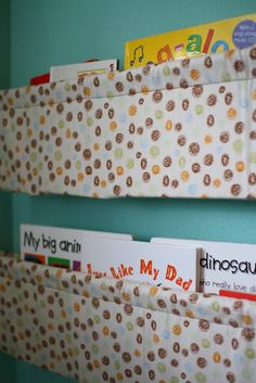 DIY book rack--uses 1 1/3 yard of fabric, double curtain rod.  link : http://pennycarnival.typepad.com/penny_carnival/2009/02/tutorial-hanging-book-display.html