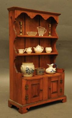 18th century cabinet in miniature containing pewter candlesticks, glass pieces and china.