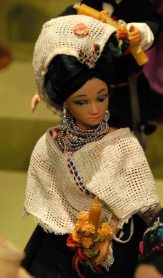 This Mexican costume doll represents a Nahua woman from the Cuetzalan region of northern Puebla state. She wears a white quechquemitl and also has another on top of her yarn headdress (maxtahual). Zuno de Echeverria doll collection