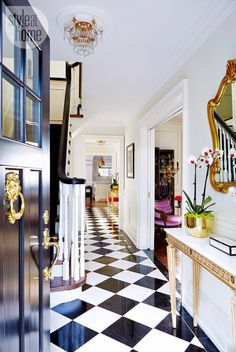black front door, gold lion door knocker, black white glam, gold, checkered floor, chandelier.