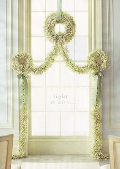 From Martha Stewart ---A trio of wreaths with swagging and a touch of ribbon used as a back drop for a ceremony.