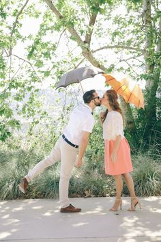 Smooch under the umbrella! 60s Inspired Pastel Engagement Photo Shoot - Pic: Taylor Abeel Photography