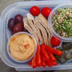 A Mediterranean-themed bento is packed with red pepper hummus, whole wheat pita wedges, Kalamata olives, red pepper strips, tabbouleh, rice-stuffed grape leaves and grape tomato fill-ins.