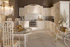 Una habitación muy importante es la cocina, que es bastante grande y muy luminosa. A la izquierda hay una pequeña mesa y alrededor de esta hay tres sillas blancas. Desde el techo cuelga una lámpara blanca muy bonita! A la derecha hay un vagòn blanco y bonito con flores. En la cocina hay muchos cajones porque está muy equipada.