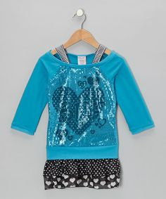 Sparkling sequins and a playfully patterned skirt make this sweet piece a standout! Comfortable and carefree, it boasts a wide neckline and soft knit that makes it perfect for a day of play.