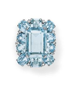 AN AQUAMARINE AND DIAMOND RING, BY CARTIER Set with a rectangular-cut aquamarine, within an oval and square-cut aquamarine surround, trimmed with single-cut diamonds, mounted in platinum, circa 1950 Signed Cartier, Paris no. L5135