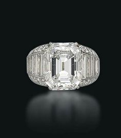 A DIAMOND RING, BY CARTIER  Set with a cut-cornered rectangular-cut diamond, weighing approximately 7.82 carats, to the pavé-set diamond raised base, graduated baguette-cut diamond line shoulders and reeded gold hoop, ring size 4½, with French assay marks for platinum and gold Signed and with maker's mark for Cartier Paris,