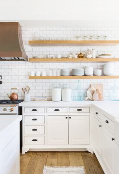 The white kitchen in Lauren Conrad's Pacific Palisades home proves that a clean, bright kitchen never goes out of style. Open wood shelving helps maintain a lighter touch overall, and, of course, we're not complaining about the white cabinets juxtaposed with a beautiful white backsplash. The floating shelves and darker hardware bring contrast and warmth for an overall inviting feel.