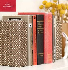 Cover bricks for bookends in beautiful fabrics that match decor. Love this idea.