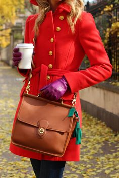 Bright winter wear, red coat, purple leather gloves and a Coach bag