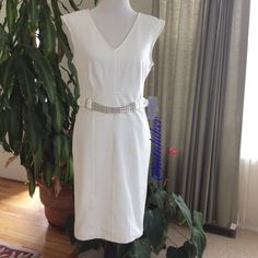 "Sleeveless White Dress NWT Host Pick Wear this gorgeous dress as part of an all white ensemble or add a pop of color with patterned shoes or a bright handbag or jacket  Pretty chain belt detail at the waistline & seaming accentuate your figure.V neckline. Back zip closure  Very nice knit fabric w/ stretch & fully lined for no show through. 75% polyester; 20% rayon; 5% spandex. Machine wash  Bust 38""; waist 32""; hip 38""; length shoulder to hem 39"". Has stretch  Love it with the Juicy wedges…"