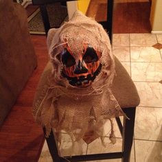 Made a scarecrow head from foam pumpkin, painted mask to look like a pumpkin, burlap material and a bunch of hot glue!