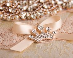 Rose gold crown charm adorn the tossing garter.