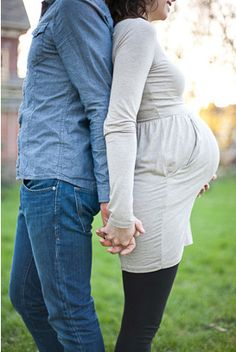 side belly shot, couple, back to back, holding hands