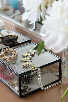 See through square jewelry box with a statement necklace on top