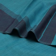 #PadmaPaaduka #Handwoven Muga Tussar Sari in Wide Diagonals of Blue & Grey Hues ~ Hues of silver clouds or rippling waves of ocean blue - which is the inspiration here? This muga tussar sari is a flowing symphony of colours as wide diagonal bands; each colour merging into the other with panache - ramar green or deep ramar blue, two tone blue-grey! In contrast, the pallu emerges as broad vertical stripes while the blouse is a creation of thinner bands. Simply, simply, simply smart!Code…