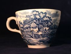 This sweet little tea cup is surrounded by a English village scene in blue - complete with cottages, bridges, chickens and flowers. Even the handle and top interior of the cup have a delicate floral design. The cup is stamped on the bottom: Alfred Meakin England.  Alfred Meakin Ltd was set up in 1875 and operated from the Royal Albert, Victoria and Highgate Potteries in Tunstall until 1976. Alfred Meakin manufactured ironstone china and white granite ware, suitable for export.  Size…