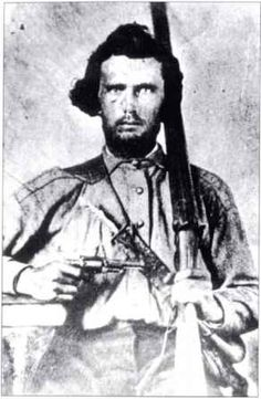 This Texan volunteer wears a battle shirt with brass ball buttons. His ammunition is carried in a hunting pouch on his right hip - the left, in this reversed image. It has a powder horn and measure, and the sling, with an unusually wide shoulder piece, carries a sheathed dirk. He holds a shotgun, and a New Model M1855 Colt Pocket revolver - the Root Patent Colt. (Research Division, Oklahoma Historical Society)