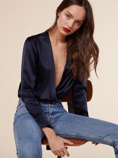 This bodysuit has a stretchy bottom, so you can look your best and still feel comfortable - Spanx but no Spanx. This is a long sleeve bodysuit with a very low v neckline and contrast fabric.