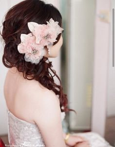 Curly hair to the side with two flowers really pretty for a wedding or something like that