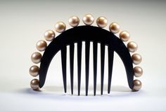 Horse-shoe shaped comb decorated with a row of huge faux-pearls contrasting with the black of the celluloid. Signed Auguste Bonaz. 1925