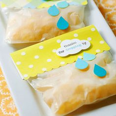 "Baby shower favors: Bags filled with lemon drop treats to thank guests for ""dropping"" by -- another homage to the ""shower"" theme. (Fill bags with small candies and top with patterned paper. Cut the bottom edge of the patterned paper with scallop-edge scissors. Add a few paper raindrops and a cloud punch with a printed sentiment to finish.)"