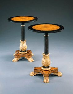 A PAIR OF REGENCY STYLE AMBOYNA AND EBONIZED OCCASIONAL TABLES Each with circular crossbanded top on columnar acanthus-carved supports on quadripartite incurving base with lion paw feet.