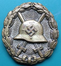 (6) German Wound Badge in Silver I Type 1939. This one has a noticeably smaller swastika and is made of brass/tombac, and having lost most of its finish. An old veteran.