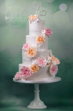 Wedding cake with cascade of rose and apricot colored roses.  By Minh Cakes in Zürich.