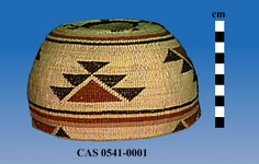 Hemispherical woman's hat with flat base and rounded sides; Woven primarily in plain twining with 3-strand twining on base; Design is in bear grass and woodwardia and maidenhair fern in half-twist overlay and is divided into 3 registers; On base or crown is central circle with 4 hooked elements; Middle and rim registers contain brown triangle bordered by stacked black triangles. Dimensions (cm)Height = 9.4, Max Diam = ca. 16.2