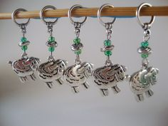 Sheep ram lamb ewe snag free no snag stitch markers These stitch markers feature fluffy sheep dangle charms, Czech glass accents in rich pastures green and silver ball of yarn accent beads (isn't that why we love sheep?) Cheery and bright! Makes you think of sunny days on the meadows! Dangle stitch markers are more than just knitting needle jewelry! Dangle markers are much easier to manoeuver from one needle to the other than single rings which are easily dropped and lost, and large bea...