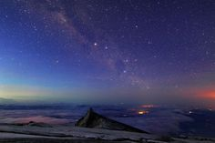 The soft lights of our Milky Way galaxy flow across the sky over Milkey Way over Mount Kinabalu, a mountain peak on the Malaysian side of the island of Borneo,