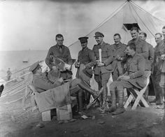 """THE BRITISH ARMY IN SALONIKA, 1915. Officers of the 26th Divisional Train with their donkey mascot """"Tiny"""" who was found dying by the roadside. The furniture was made by one of the officers out of biscuit boxes and canvas padded with hay.WW1"""
