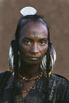 "Africa | Portrait of a Wodaabe woman with traditional silver earrings, braided hair and facial tattoos, Tahoua, Niger | © Steve McCurry, from his ""The Sahel Desert"" Album #braids #tattoo"
