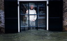 A man keeps an eye on rising water from inside his home in Dordrecht in the Netherlands on January 5, 2012.